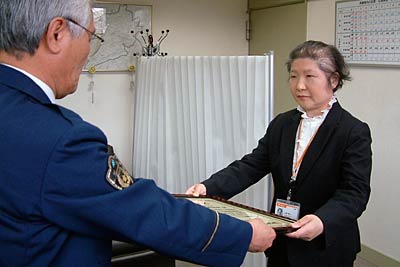 Director Yamasaki of the Kugami post office which receives a letter of thanks from Mayor of Yawata Tsubame Police Department.